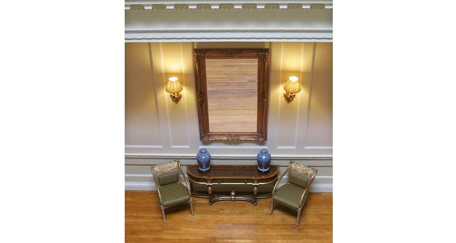 Wooden floor with two green chairs and two blue pots plus large guilt mirror