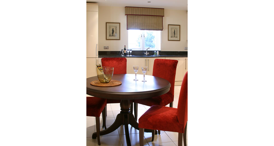 Red chairs around dark wood dining table