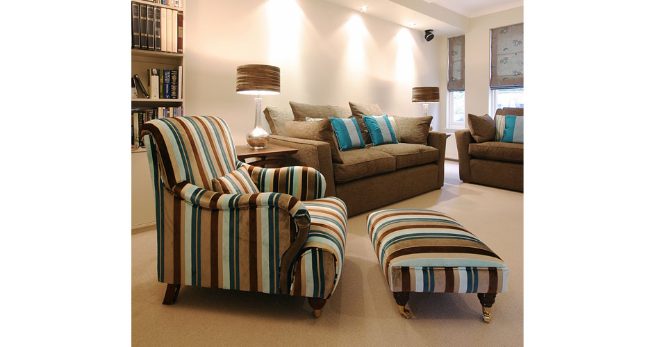 Brown sofa with blue cushions and stripey pouf